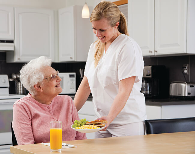 Nurse in white scrubs serving a meal to an older woman in the kitchen in Dallas, TX