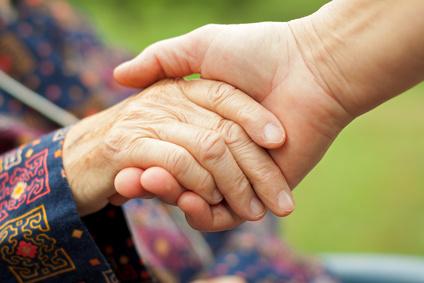 Doctor's hand holding a wrinkled elderly hand