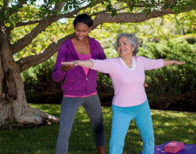 Senior woman wearing pink doing yoga outside with a home care provider in Dallas, TX