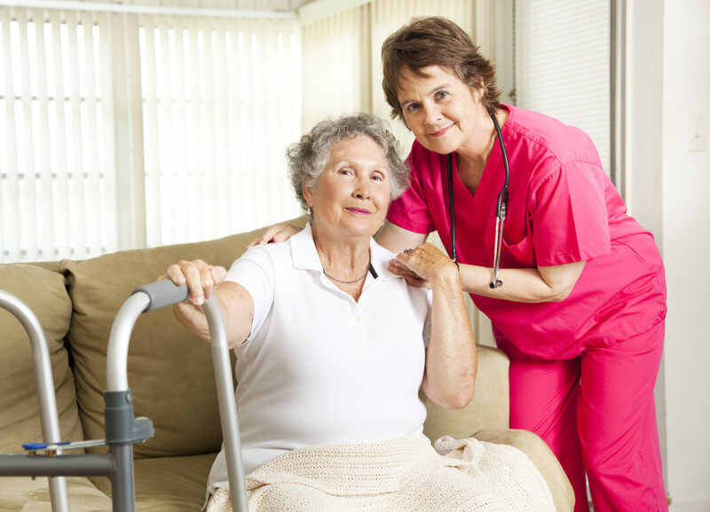 Home care provider in pink scrubs with an older woman in the living room in Dallas, TX