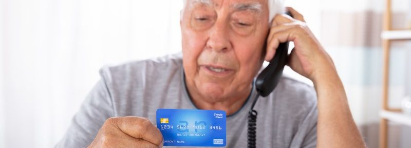 Older man with a credit card and phone in Dallas, TX