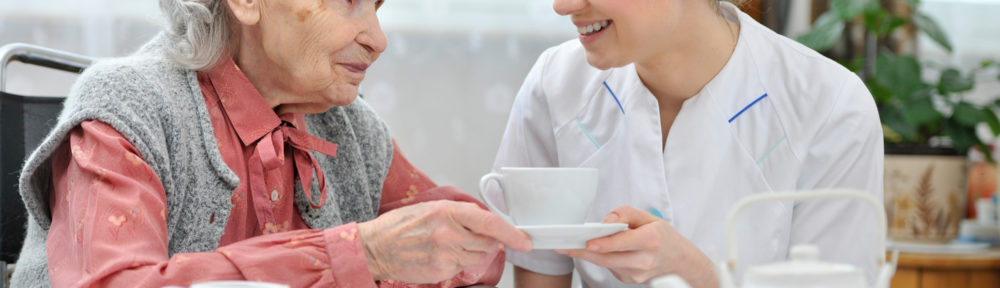 Home care provider having coffee with an older woman in Dallas, TX